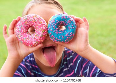 Little girl is eating colored donuts.