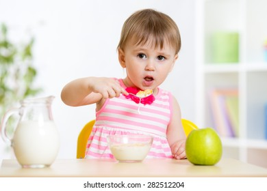 Little girl eating cornflakes with milk at table in home