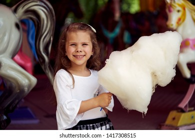 Little girl eating cotton candy at amusement park. The girl holding a candyfloss in his hand and looking into the camera.