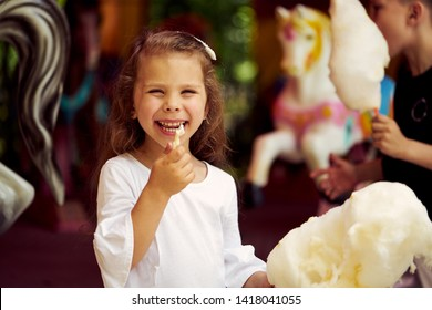 Little girl eating cotton candy at amusement park. The girl holding a candyfloss in his hand and looking into the camera and smile.