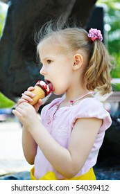 Little girl eating a delicious ice cream in waffle cone