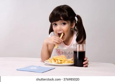 Little girl eating french fries - Shutterstock ID 376985020