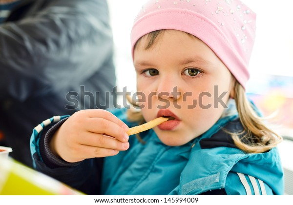 Little girl eating french fries at fast food restaurant