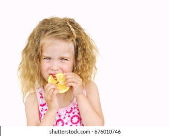 Little girl eating fresh lemon isolated on white background.