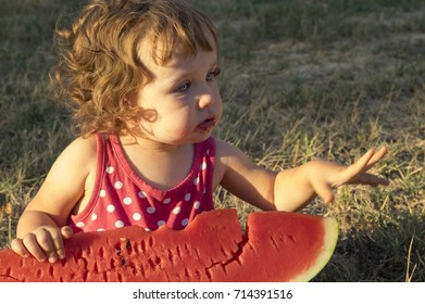 Little girl eating giant slice of ripe summer watermelon