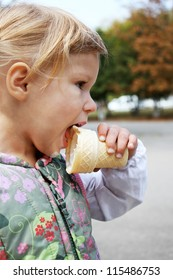 little girl eating ice cream on the nature
