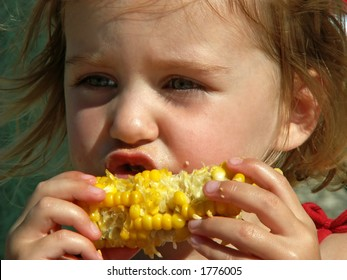 little girl eating messy corn on the cob