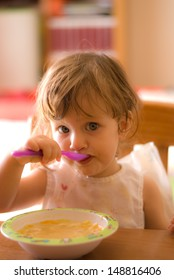 The little girl eating  on the table