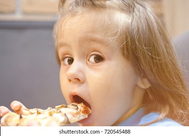 little girl is eating pizza in a cafe