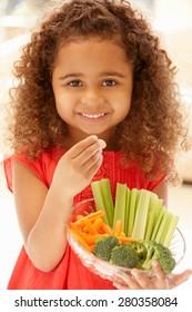 Little girl eating raw vegetables