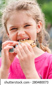 A little girl is eating a s'more made from graham crackers, roasted marshmallows and chocolate.   Her mouth is messy and she is taking a toothy bite of the s'more.