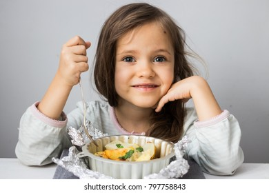 Little girl eating spicy baked potato with onion, parsley, herbs from baking dish. Vegan, vegetarian healthy food.