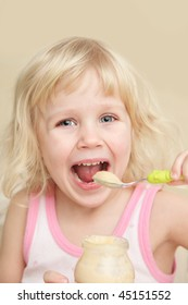A little girl eating with a spoon