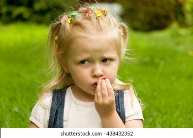 little girl eating a strawberry in nature. in the park