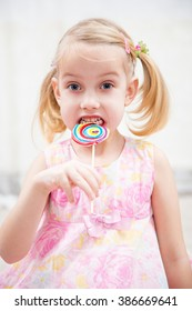 little girl eating sugar candy