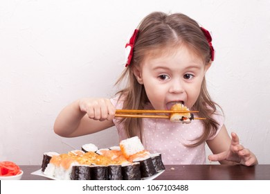 little girl eating sushi chopsticks