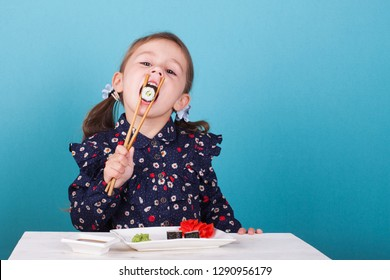 little girl eating sushi chopsticks
