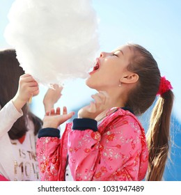 Little girl eating sweet cotton candy outside