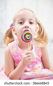 little girl eating a tasty sugar candy