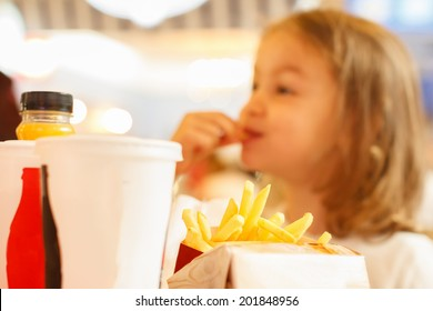 Little girl eating unhealthy fast food french fries and drink coke cola