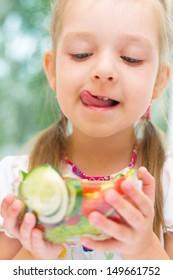 Little girl eating vegetable salad