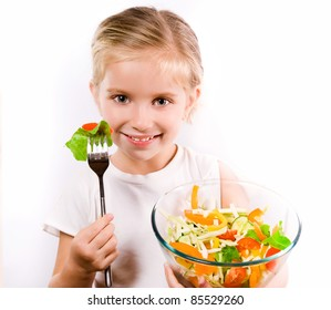 Little girl eating vegetable salad - healthy food concept