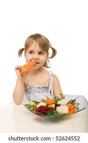 little girl eating vegetables - chomping a carrot - isolated