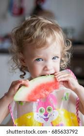 Little girl eats a juicy watermelon with pleasure