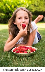 Little girl eats red strawberries
