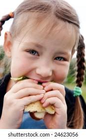 Little girl eats a sandwich on fresh air