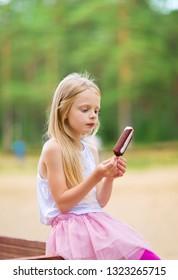 Little girl eats stick ice cream bar eskimo pie outdoors