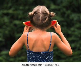 The little girl eats a watermelon