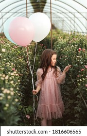 Little girl in elegant dress carrying balloons admiring flowers while celebrating birthday in hothouse