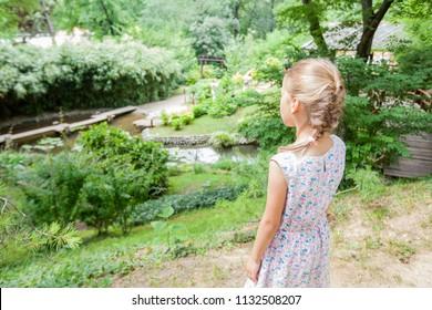 Little girl in elegant dress enjoy nature on spring day in park