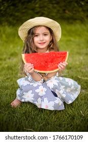 Kleines Mädchen in einem eleganten Kleid und Hut isst eine Wassermelone. Sommer, sonniger Tag, Glück