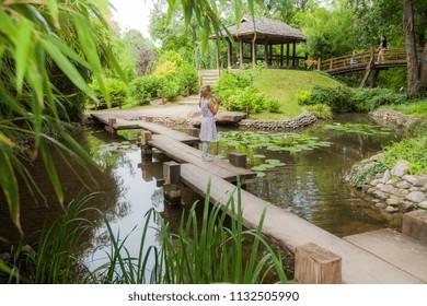 Little girl in elegant dress walk on wooden bridge over ponds in nature, spring day outdoor