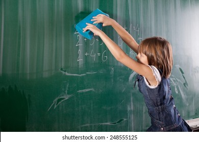 Little girl in elementary school cleaning board with sponge. Mathematics task is written on chalkboard