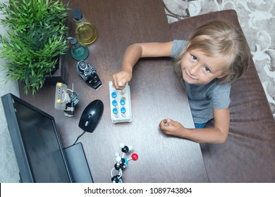 A little girl in elementary school constructs a model of a molecule and conducts simple chemical experiments. A microscope, test tubes, a metal robot are on a table. STEM education. AI.