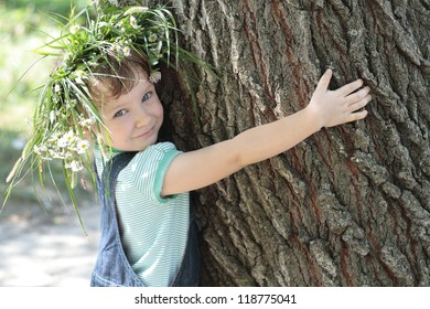 The little girl embraces a big tree