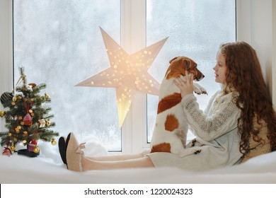 Little girl embracing her puppy dog, sitting on window and waiting Christmas.