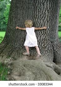 Little Girl embracing Huge Tree