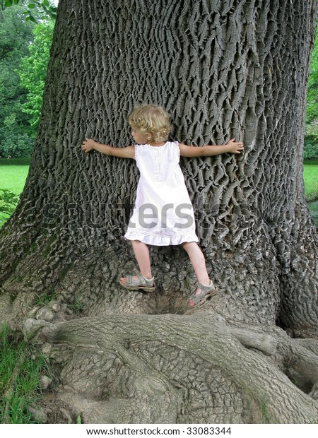 Little Girl embracing Huge Tree