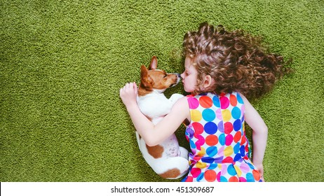 Little girl embracing puppy jack russell. High top view.