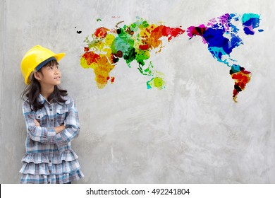 Little girl engineering with watercolor world map on wall