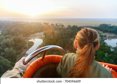 Little girl enjoying early morning flight on hot balloon in Masai Mara national park, Kenya
