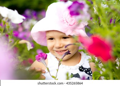 little girl enjoying flowers and their aroma,