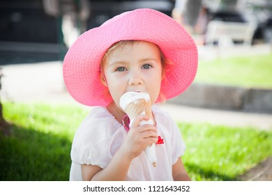 Little girl is enjoying and holding melting ice cream in cones in her hands. Child is eating gelato in resort outdoors in town streets. Kid is in pink hat. Concept of childhood, summer, traveling.