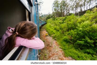 Little girl enjoying train ride from Ella  to Kandy among tea plantations in the highlands of Sri Lanka