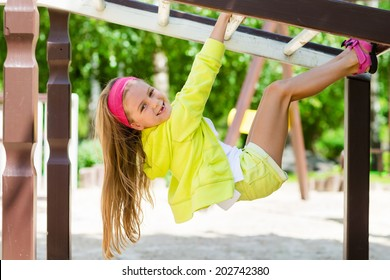 little girl enjoys playing in a children playground, Outdoor portrait