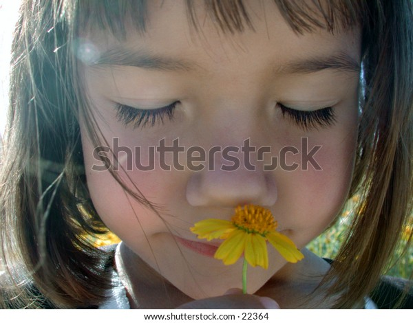 A little girl enjoys a quiet moment smelling the perfume of a wild flower.